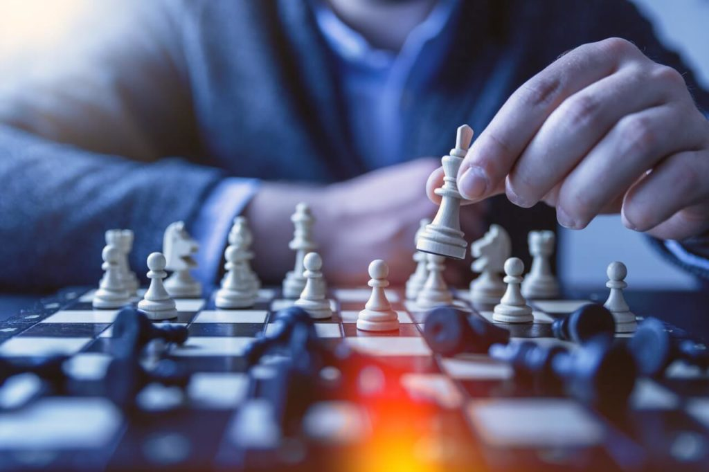 12 Steps to Moving Old Blog Posts, when, where and how. Image shows a person moving a chess piece on a chess board.